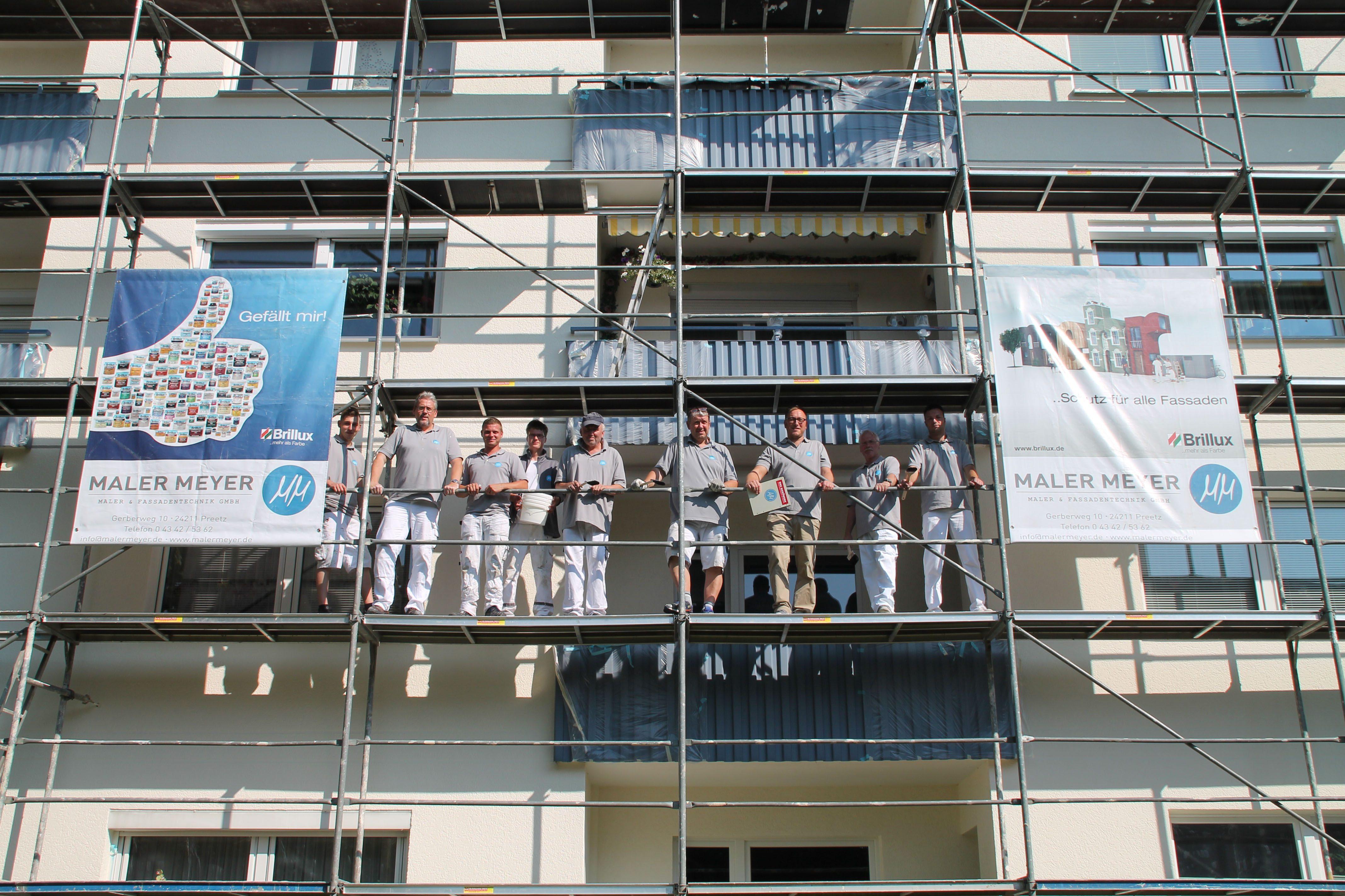 Nicki Meyer (Dritter von rechts) mit seinen Mitarbeitern bei einer Fassadenüberarbeitung in Schwentinental. Die Arbeiten reichen von der Gerüststellung über die Fassadenreinigung, die Grundierung, den Zwischenanstrich bis zum Schlussanstrich.